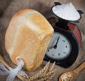Frisches Brot und Skalen mit Mehl — Stockfoto