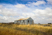 Old abandoned farm in field — Stock Photo