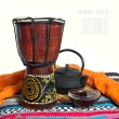Ethnic drum and black tea — Stock Photo