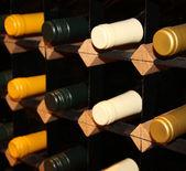 Wine bottles stacked on wooden racks. Shallow depth of field — Stock Photo