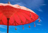 Orange beach umbrella umbrella on sky background, — Stock Photo