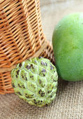 Green fresh mango and custard apple — Stock Photo