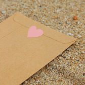 Congratulatory envelope on the beach — Stock Photo