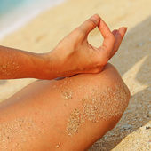 Woman meditating on the beach — Stock Photo