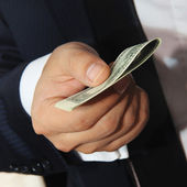 Businessmen holding money 100 dollars proposing it to you — Stock Photo