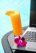 Black laptop and orange juice poolside — Stock Photo