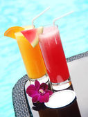 Two glasses of juice with a card by the swimming pool with space for text — Stock Photo