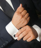 A man in a black suit straightens his  cufflinks — Stock Photo