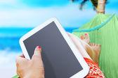 Vrouw rustend op de zee met een witte tablet — Stockfoto
