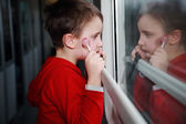 Child with dreamy eyes facing out the window of a train. — Stock Photo
