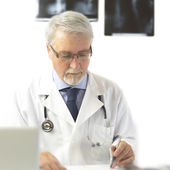 Doctor writing a prescription, on the white background with x-ra — Stock Photo