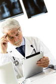 Doctor in clinic sitting at desk looking at x-rays on tablet — Stock Photo