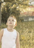 Child looks intrigued into the sky — Stock Photo