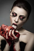 Beauty young woman licks blood from human heart — Foto de Stock
