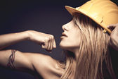 Sexy young woman with safety helmet showing muscles — Stock Photo