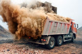 Dust explosion when loading red truck at the mine — Stock Photo