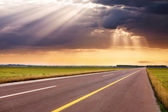 Driving on empty highway towards the sunbeams — Stock fotografie