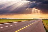 Köra på tom motorväg mot solstrålar — Stockfoto