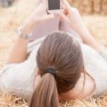 Brunette teen girl sending a text lying on a haystacks — Stock Photo