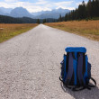 Backpack on the road leading into the mountains — Stock Photo