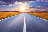 Driving on an empty road towards the setting sun — Stock Photo