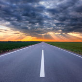 Driving on an empty road towards the storm — Stockfoto