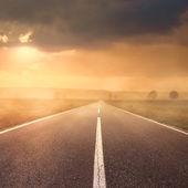 Jízdy na asfaltovou silnici při západu slunce k slunci ii — Stock fotografie