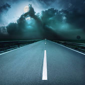 Driving on asphalt road towards oncoming stormy night — Stok fotoğraf