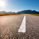 Driving on asphalt road towards the sun — Stock Photo