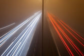Night traffic on a highway in the fog — Stockfoto