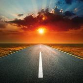 вождение на пустой дороге против заходящего солнца — Стоковое фото