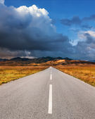 Driving on an empty asphalt road to the mountains  — Stock Photo