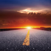 Driving on an empty country road at sunset — Stock Photo