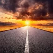 Conduisant sur une route vide vers le soleil couchant — Photo