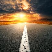 Driving on  asphalt road towards the setting sun — Stock Photo
