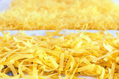 Raw pasta strewn on table for drying — Stock Photo