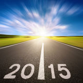 Motion blurred asphalt road forward to 2015 — Stock Photo