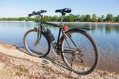 Bike on the shore of crystal clear lake — Stock Photo