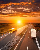 Two trucks on the highway at sunset — Foto de Stock