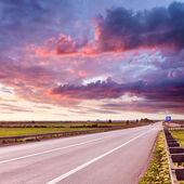 Driving on an open asphalt road at sunset — Foto Stock