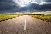 Driving on an empty aspalt road towards the sunlight — Stock Photo