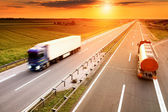 Two trucks in motion blur on the highway — Stock Photo
