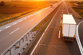 Truck and bus in motion blur at sunset — Stock Photo