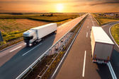 Two trucks on highway in motion blur — Stock Photo