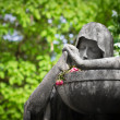 Mourning statue with withered flowers — Stock Photo