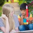 Boy and girl writing and reading together in the garden — Stock Photo