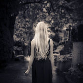 Blond girl walking alone in the dark at cemetery — Stock Photo