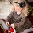 Cute girl playing with Santa and golden pearls — Stock Photo