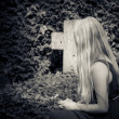 Stock Photo: Young girl with long blond hair in front of green grave