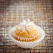 Little cupcake decorated with powdered sugar and little gumpaste flower — Stock Photo